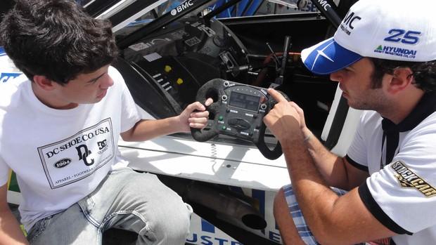 Tuka Rocha mostra o volante de um Stock Car para o piloto virtual Matheus Nunes (Foto: Rodrigo França/ RF1)
