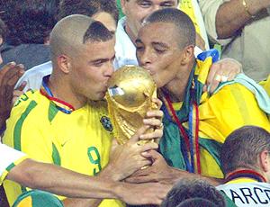 Gilberto Silva beija a taça de campeão do mundo em 2002,  ao lado   de Ronaldo
