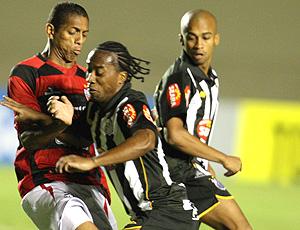 Arouca, do Santos, disputa a bola com o zagueiro do Atlético-go