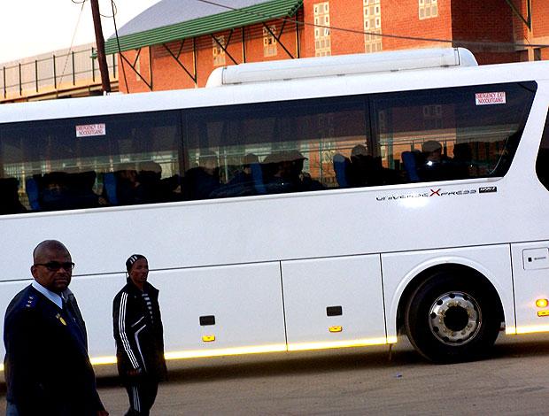 policial Badimo (E) e chegada do ônibus da Coreia do Norte