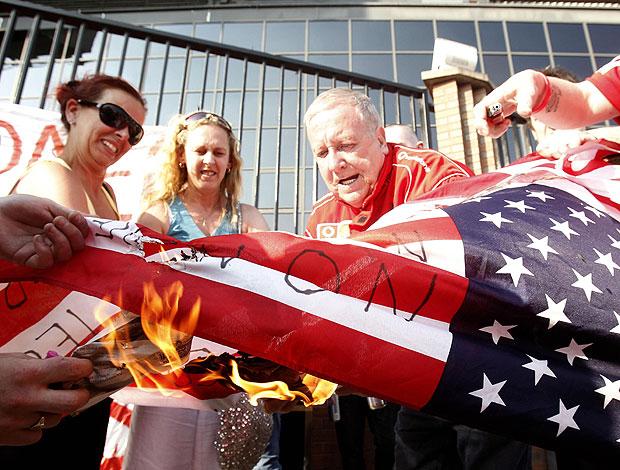 torcedores do Liverpool queimam a bandeira americana em protesto