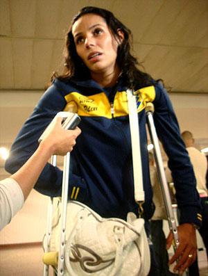Paula Pequeno de muletas no desembarque da seleção feminina de vôlei