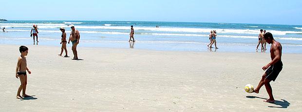 Lucas na praia jogando bola com criança