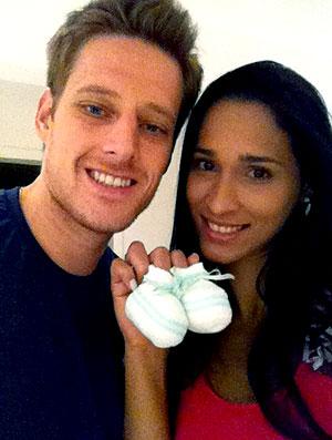 Jaqueline e Murilo do vôlei com os sapatinhos do bebê (Foto: Divulgação)