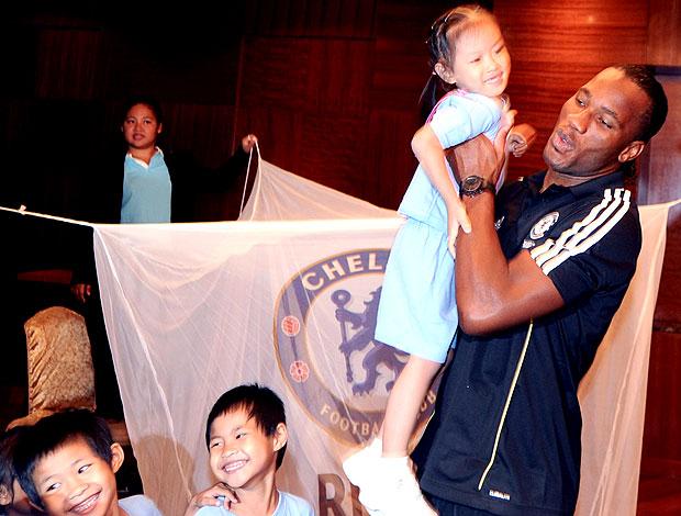 Drogba posa com crianças carentes na Malasia (Foto: AFP)