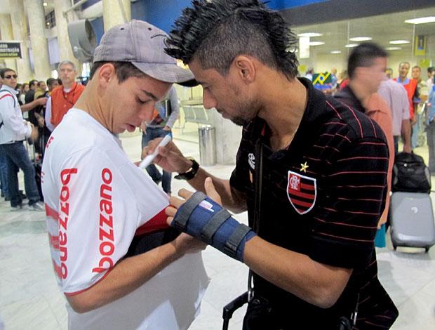 Léo Moura com a mão imobilizada no desembarque do Flamengo (Foto: Janir Junior / Globoesporte.com)