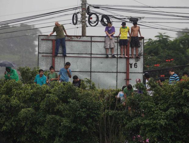 Torcedores sobem em placa para ver o treino da seleção brasileira (Foto: Mowa Press)
