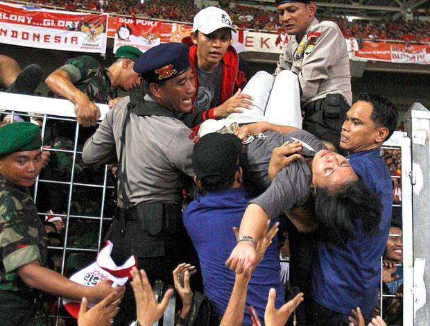 torcedora é retirada por policiais em confusão na partida da Malásia contra a Indonésia (Foto: AP)