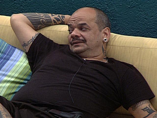 A blusa preta e colada exibe a barriga acentuada de João Carvalho