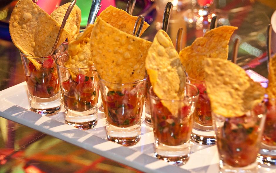 Copinhos de guacamole com salsa de tomate para acompanhar os nachos