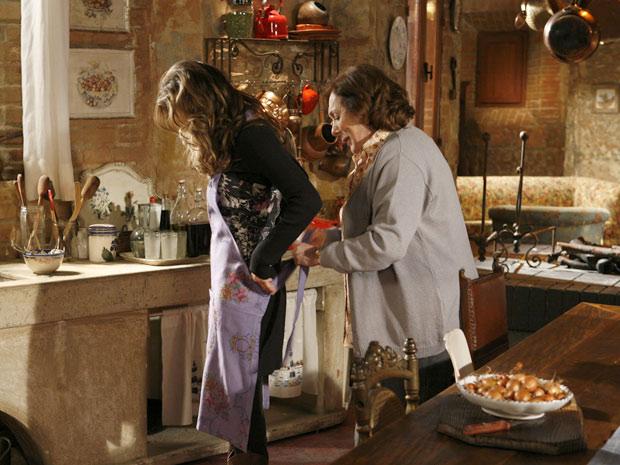 Gemma coloca Clara para lavar a louça e a ajuda a com o avental de cozinha