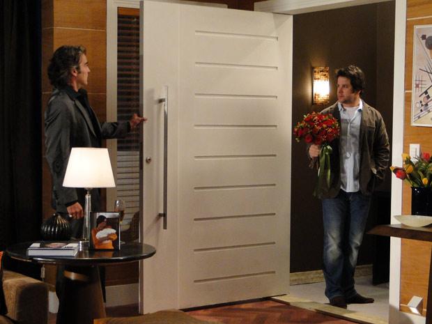 O estilista abre a porta para Suzana e dá de cara com Ariclenes