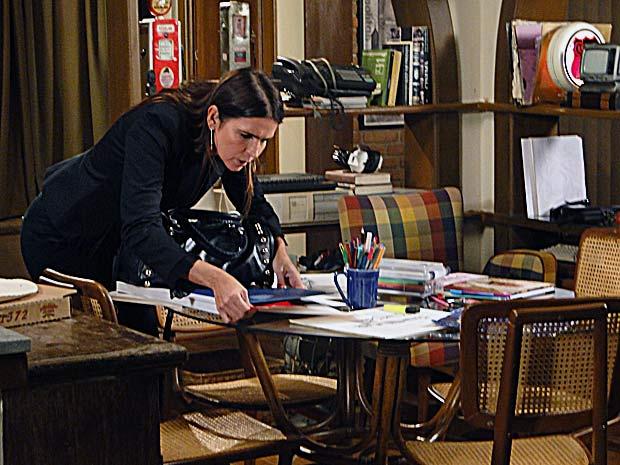 Ela vai arrumar a mesa e acha uma ponta de um papel com uma amostra de tecido vermelho