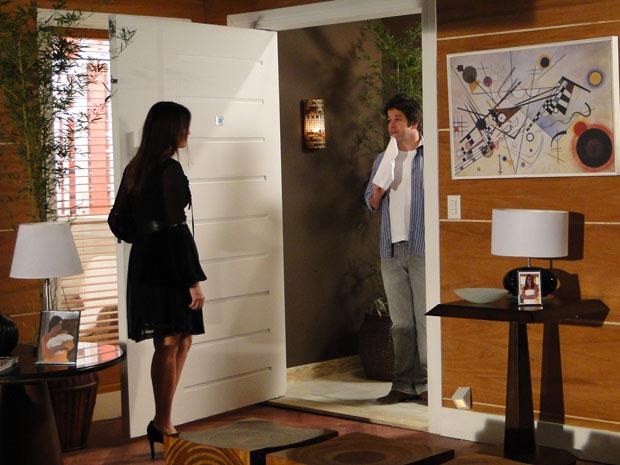 Suzana abre a porta para sair e dá de cara com Ari segurando uma bandeira branca
