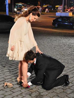 Ela se ajoelha aos pés dela e calça o sapato que guardava