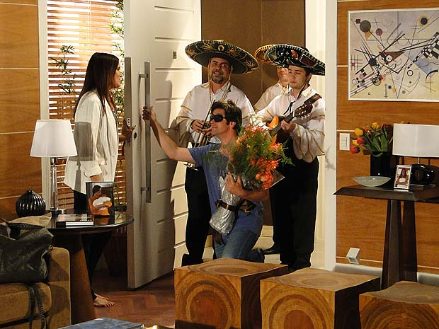 Ari aparece na casa de Suzana com um buquê de flores e um trio de músicos