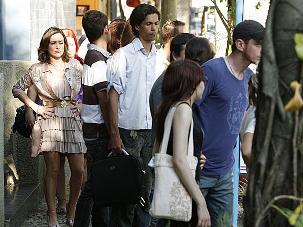 Jéssica olha com nojo para as pessoas à sua volta na fila do ponto de ônibus