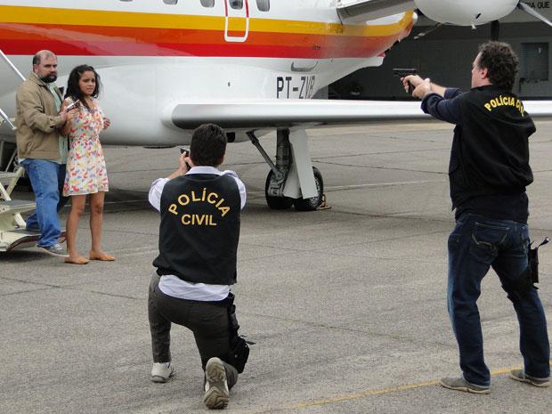 Polícia cerca o avião e Totó tenta negociar com Jonisval que aponta uma arma para a cabeça de Kelly