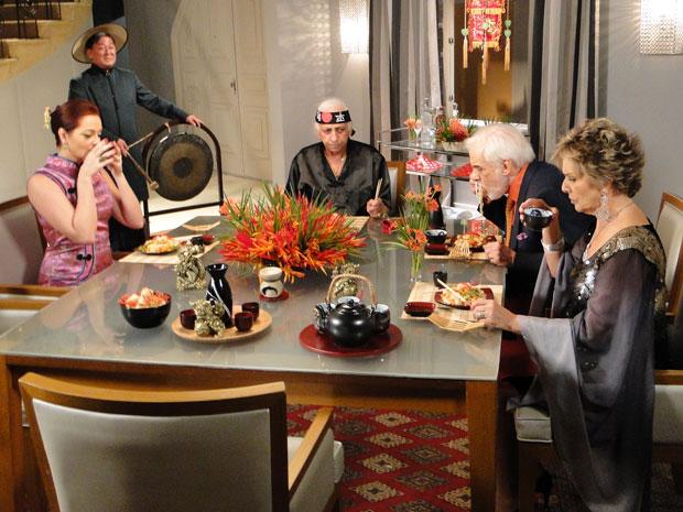 Vestidos como chineses, Jackie e Fortunato recebem Clô e Olavo