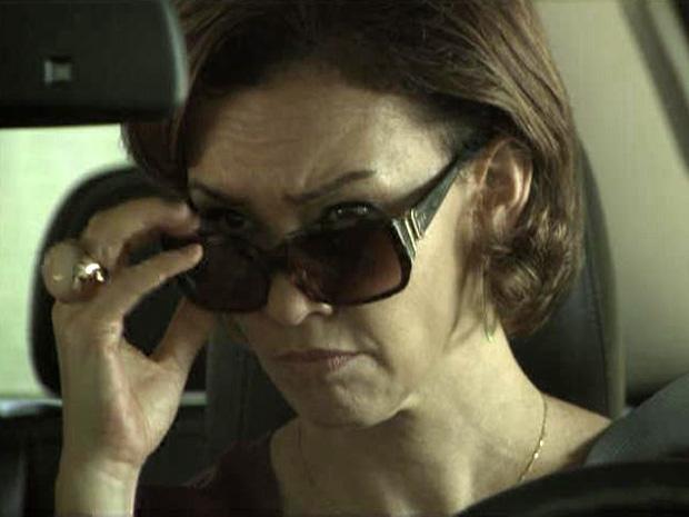 Amélia olha o retrovisor e percebe que está sendo seguida