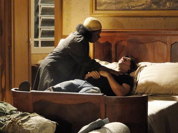 Para acalmá-lo, ela o deita sobre a cama do quarto de hotel
