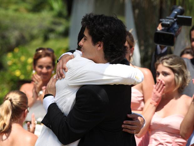 Os dois se abraçam sob os aplausos dos convidados