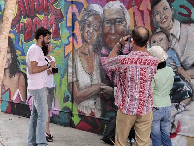 Um casal de turistas faz fotos do muro antes da destruição de Luisa