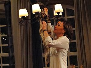 Amélia tira a lâmpada do lustre e, depois, a do abajur