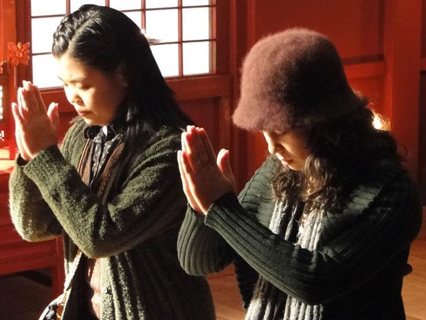 Keiko e Hoshi oram em um templo japonês