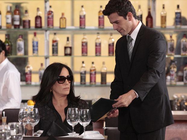 Em uma mesa distante, Norma pega informações sobre Marina com o maître