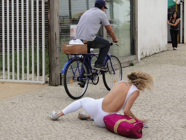 Ciclista atropela Natalie e Norma, ao fundo, aguarda para socorrer a loira