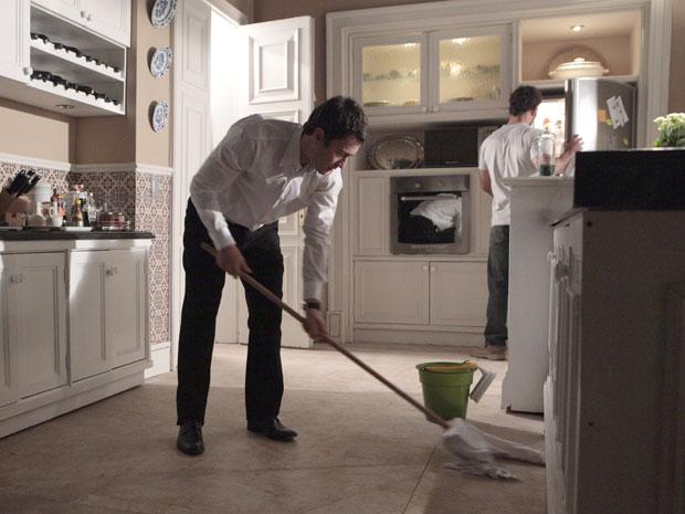 Léo limpa o chão da cozinha, quando Ismael chega e oferece uma bebida ao vilão (Foto: Insensato Coração / Tv Globo)
