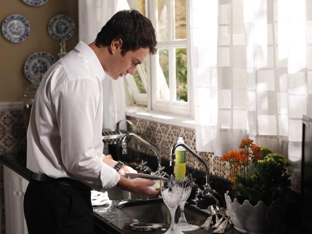 Léo lavando louça, ensimesmado (Foto: Insensato Coração/TV Globo)