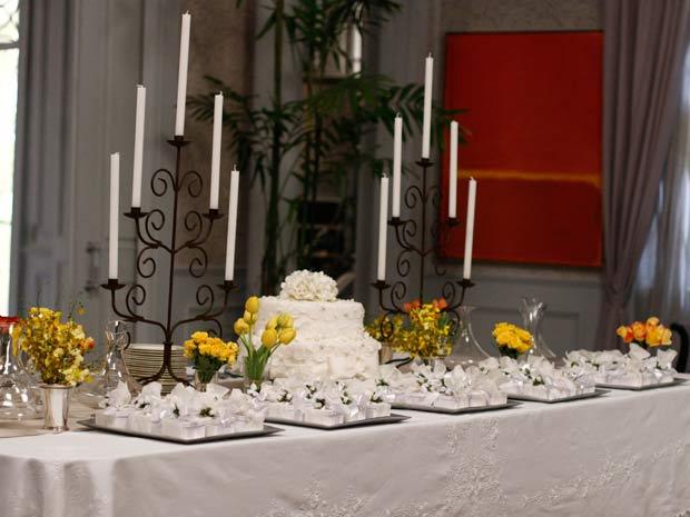 A mesa do bolo foi decorada nas cores branca e amarela. As tulipas dão o ar sofisticado da decoração e as velas conferem romantismo à festa