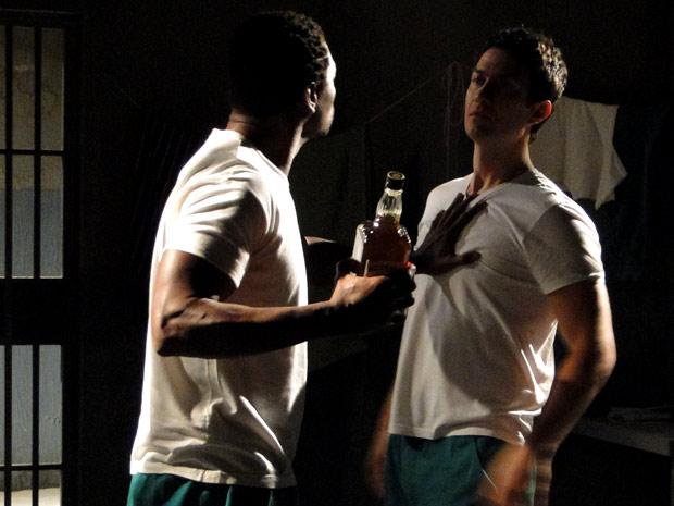 O companheiro mal-encarado tira a garrafa de Léo e o empurra (Foto: Insensato Coração / TV Globo)