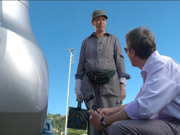 Griselda vê que Renê precisa de ajuda com troca de pneu (Foto: Fina Estampa/TV Globo)