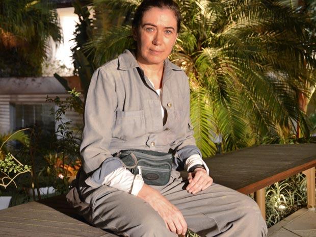 A personagem de Lilia Cabral usa um macacão de brim cinza e boné (Foto: Fina Estampa/TV Globo)
