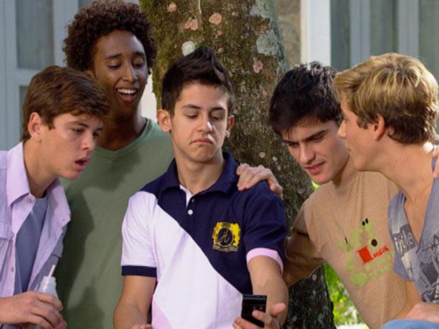 Amigos de René Junior ficam espantados com a foto no celular do amigo (Foto: Fina Estampa / TV Globo)