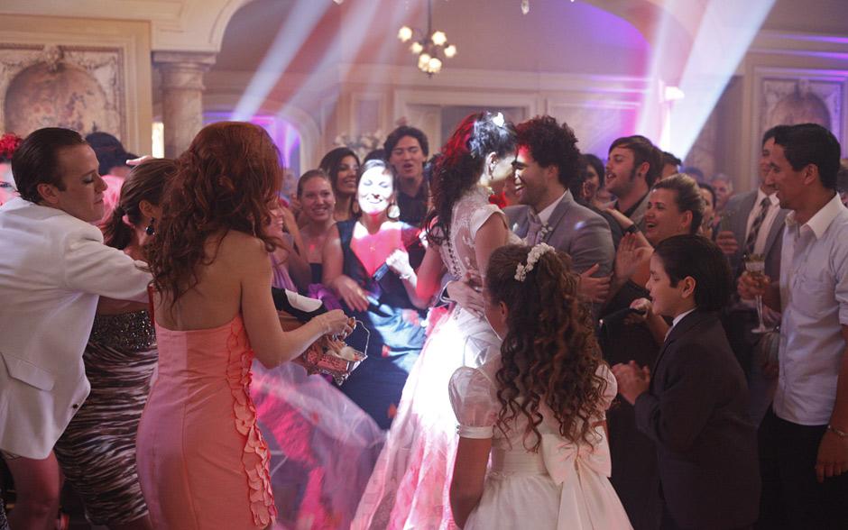 O casal se acaba na pista de dança junto aos convidados