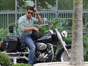 O modelo chega de moto à faculdade onde Letícia dá aulas (Foto: Fina Estampa/TV Globo)