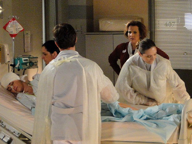 Eva observa enfermeiras e reclama do lençol mal esticado (Foto: A Vida da Gente/TV Globo)
