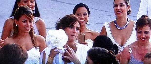 Sem querer, Claudia pega o buquê de Lucena (Foto: Aquele Beijo/TV Globo)