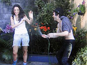 Agenor dá banho de mangueira em Belezinha (Foto: Aquele Beijo/TV Globo)
