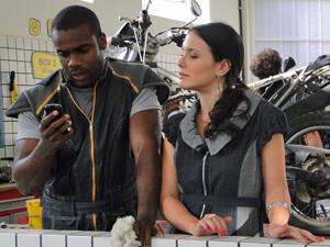 A recepcionista mostra fotos para Edvaldo (Foto: Fina Estampa/TV Globo)