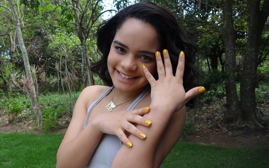 Solange esbanja alegria: ela usa um esmalte amarelo com uma cobertura de glitter dourado!