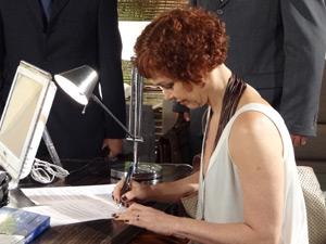 Esther assina o destrato (Foto: Fina Estampa/TV Globo)