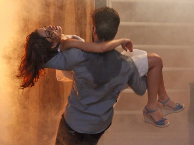 Ele corre com a amada em seus braços antes que o fogo se alastre ainda mais (Foto: Fina Estampa/TV Globo)