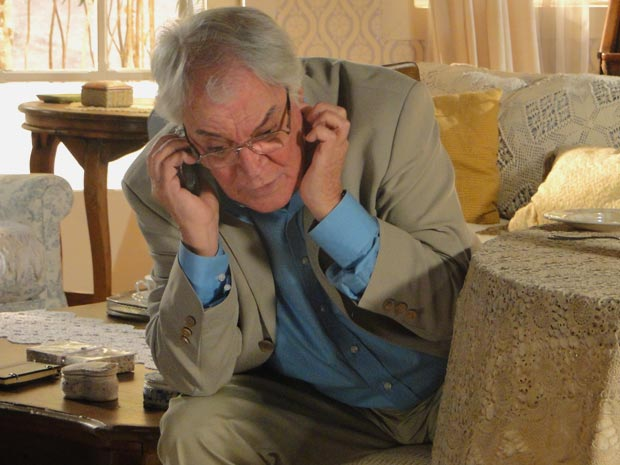 Ele fala ao telefone com Moema, enquanto Aurélia pega a sobremesa (Foto: A Vida da Gente/TV Globo)