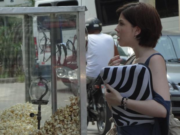 Alexia vê pelo espelho do pipoqueiro que Carcará está na sua cola (Foto: Malhação / TV Globo)