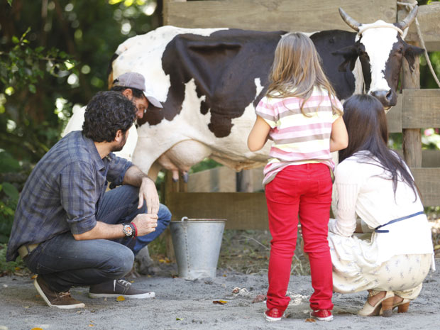 Ao lado de Manu, Júlia observa encantada um funcionário de Gabriel ordenhado a vaca (Foto: A Vida da Gente / TV Globo)